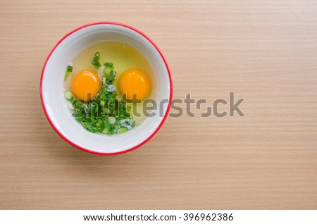 Raw eggs and onions In a bowl on wooden table.Right copy space. - stock photo