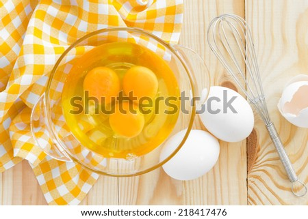 Raw eggs and whisk - stock photo
