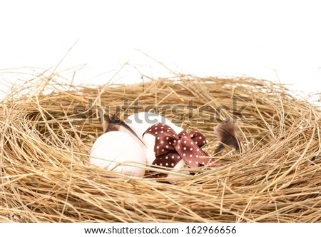 Raw eggs decorated with ribbon in a birds nest with feathers over white background