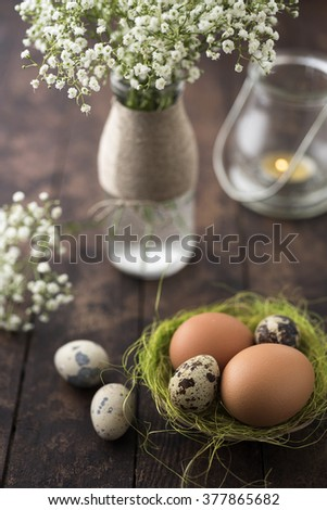 Raw eggs in a basket with flowers - stock photo