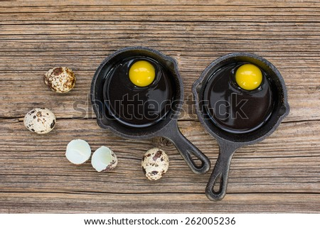 Raw eggs in frying pan, quail eggs, eggshell on wooden background - stock photo