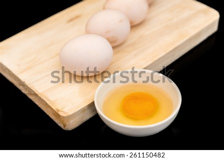 raw eggs, raw eggs in a bowl black background - stock photo