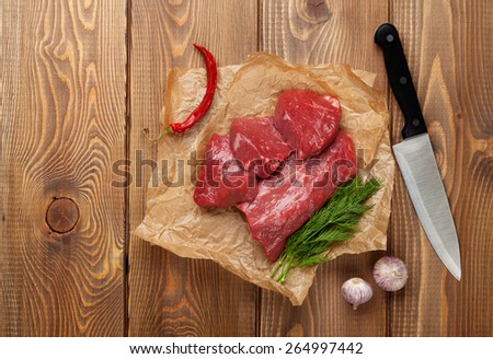 Raw fillet beef steak and spices on wooden table. Top view with copy space - stock photo
