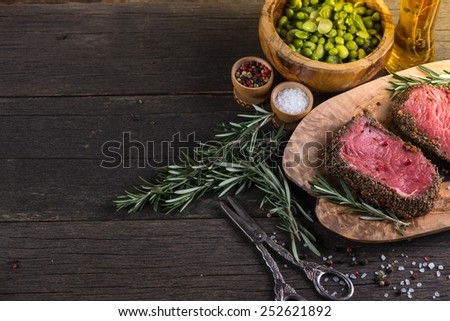 Raw fillet beef steak with herbs and salad - stock photo