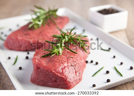 Raw fillet with rosemary and pepper - stock photo