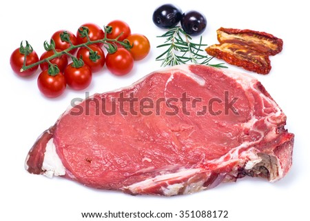 Raw fiorentina steak with spices and vegetables isolated on a white background. Selective focus with shallow depth of field - stock photo