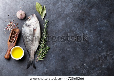 Raw fish cooking and ingredients. Dorado, herbs and spices. Top view with copy space on stone table