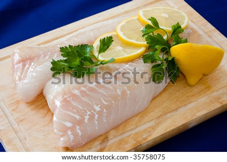 Raw fish fillet with lemons - stock photo