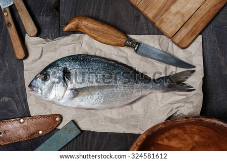 Raw fish on the wooden table with accessories