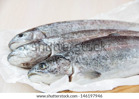 Raw fish rainbow trout prepared for baking in frying pan - stock photo