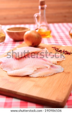 Raw fish tlapia on cutting board surrounded by spices and seasonings, selective focus - stock photo