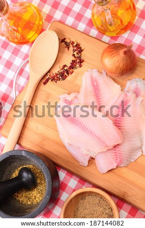Raw fish tlapia on cutting board with spices and seasonings, selective focus - stock photo