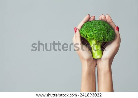 Raw food concept. Woman's hands holding bunch of broccoli over light gray background. Close up. Copy-space