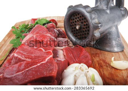 raw fresh beef meat fillet on a wooden plate with dill , hot green red peppers, and grinder isolated over white background - stock photo