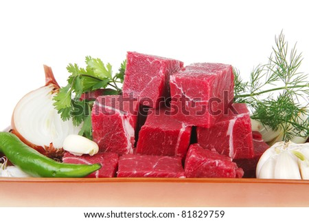 raw fresh beef meat slices in a ceramic dish with garlic and peppers isolated over white background - stock photo