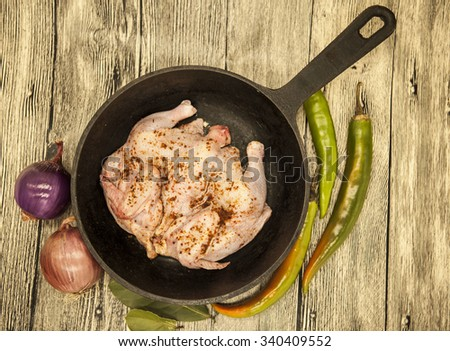 Raw fresh chicken on iron pan  with chili pepper and onions over wooden background - stock photo