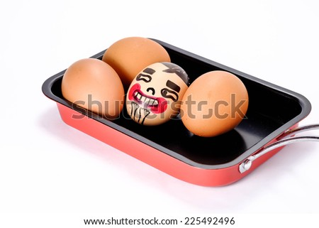 Raw fresh eggs with funny face on pan - stock photo