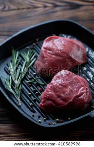Raw fresh fillet mignon beefsteaks on a cast-iron grill, close-up - stock photo