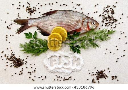 """raw fresh fish on marble table with lemon, pepper, dill and parsley. Pile of salt with word """"fish"""". Crucian fish. top view, flat lay. - stock photo"""