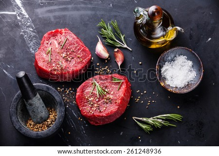 Raw fresh marbled meat Steak and seasonings on dark marble background  - stock photo