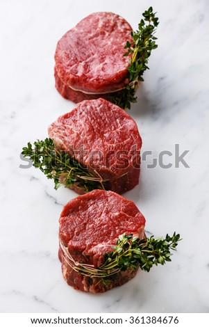 Raw fresh marbled meat Steak filet mignon and thyme on white marble background - stock photo