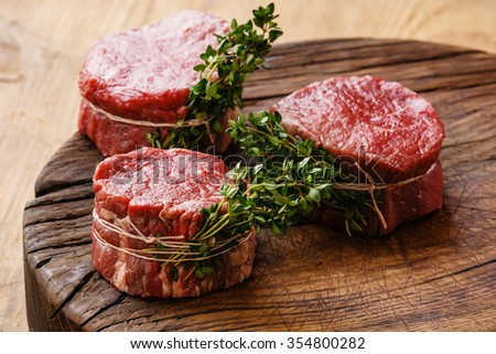 Raw fresh marbled meat Steak filet mignon and thyme on wooden background - stock photo