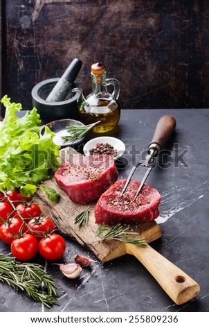 Raw fresh marbled meat Steak, seasoning and meat fork on dark marble background