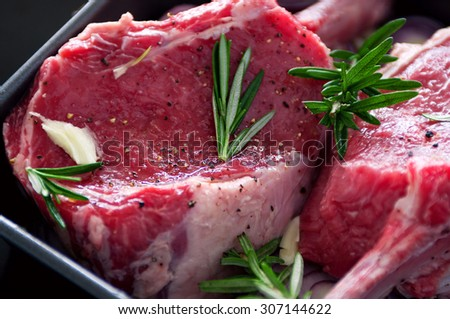 Raw fresh meat beef steak, seasonings with salt, pepper, rosemary leaves and red onion, on a black tray ready to be cooked, top view, copy space