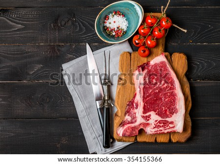 Raw fresh meat Club Steak, seasoning and meat fork and knife on dark wooden background, top view - stock photo