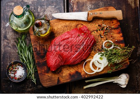 Raw fresh meat filet and condiments on dark background - stock photo