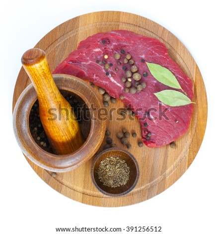 Raw fresh meat on board with condiments on white background - stock photo