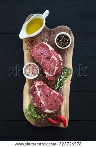 Raw fresh meat Rib Eye steak entrecote and seasonings on cutting board on dark wooden background, top view - stock photo