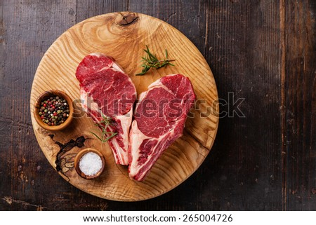 Raw fresh meat Ribeye Steak with rosemary, pepper and salt on dark wooden background - stock photo