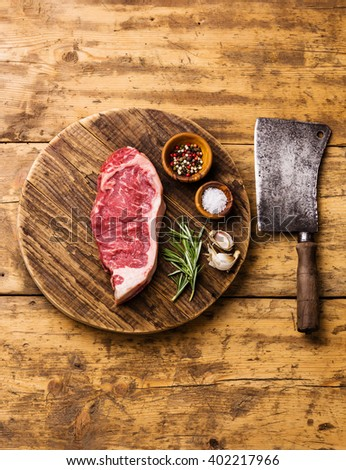 Raw fresh meat steak Striploin with salt and pepper and Butcher Meat cleaver on cutting board on wooden background - stock photo