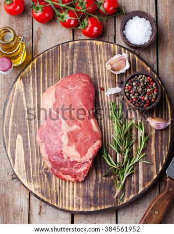 Raw fresh meat Steak with salt and pepper, rosemary and tomatoes on cutting board on dark wooden background Copy space Top view - stock photo