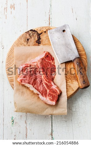 Raw fresh meat T-Bone Steak and meat cleaver on cutting board on blue background - stock photo