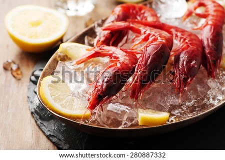 Raw fresh shrimps with ice and lemon, selective focus - stock photo