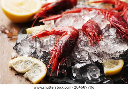 Raw fresh shrimps with ice and lemon, selective focus