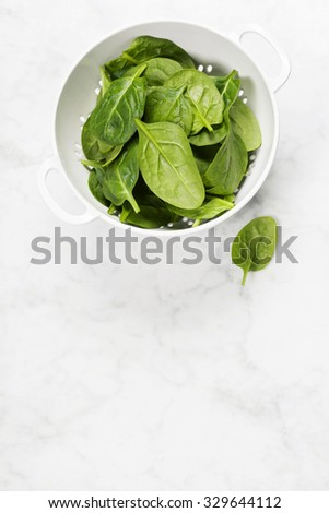 raw fresh spinach in a colander