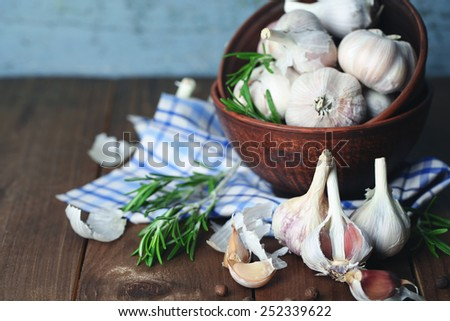 Raw garlic and spices on wooden table - stock photo