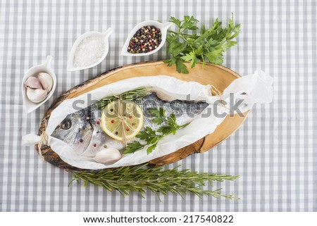 Raw gilt-head sea bream with herbs and spices in a bakery release paper prepared to be cooked - stock photo