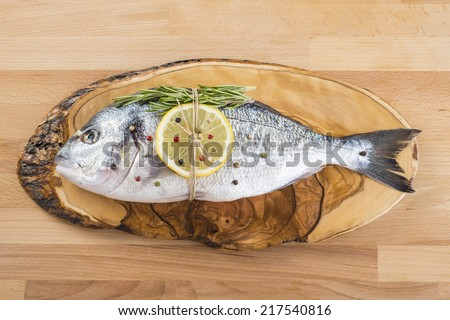 Raw gilt-head sea bream with spices and herbs on a cutting board ready to be cooked - stock photo