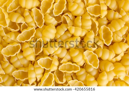 Raw gnocchi yellow pasta background - stock photo