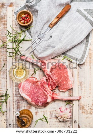 Raw gourmet pork cutlet for grill,BBQ or cooking with herbs ,spices and meat fork on light rustic background, top view.  Porco Iberico French Racks. Meat food.  Pork rib chop with bone. - stock photo
