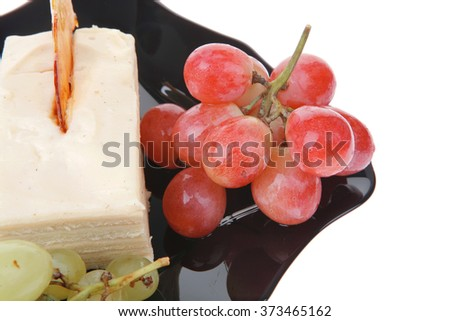 raw grapes and cream cake on black over white - stock photo