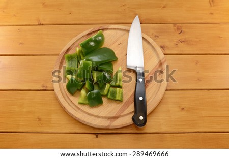 Raw green pepper being cut into pieces with a sharp kitchen knife on a wooden chopping board - stock photo