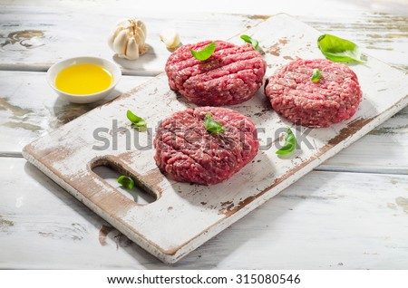 Raw Ground beef Burger steak patties on white wooden cutting board. Selective focus - stock photo