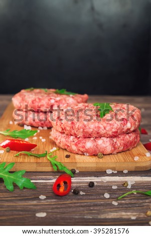 Raw ground beef burgers with chili pepper and arugula on rustic wooden table. Selective focus. - stock photo