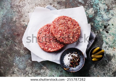Raw Ground beef meat Burger steak cutlets and seasonings on metal background - stock photo