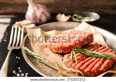 Raw Ground beef meat Burger steak cutlets on a black background stone.  - stock photo
